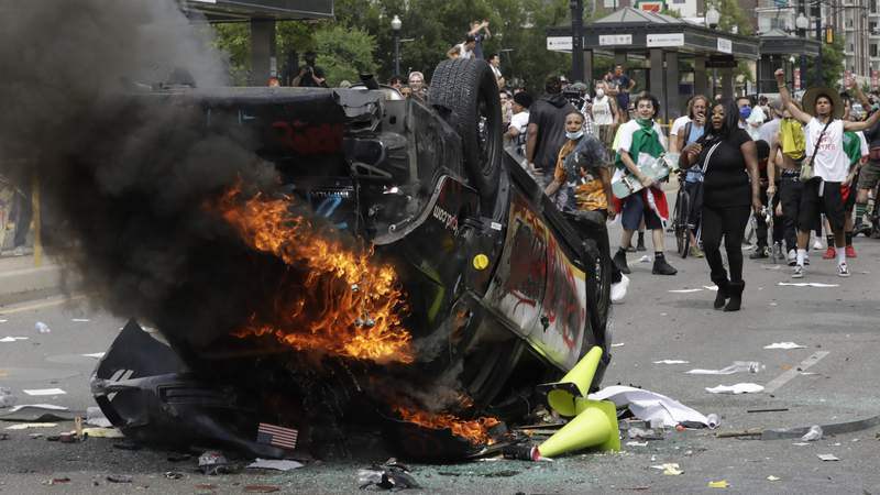 FILE - In this May 30, 2020, file photo, protesters demonstrate as a Salt Lake City police vehicle burns, in Salt Lake City. Investigators studied video footage to find Jackson Stuart Tamowski Patton, 26, who is accused of tossing a combustible substance into the patrol car, feeding the flames that destroyed it, prosecutors said in court documents. The Department of Justice is using aggressive tactics against those it has charged in the civil unrest over racism. (AP Photo/Rick Bowmer, File)