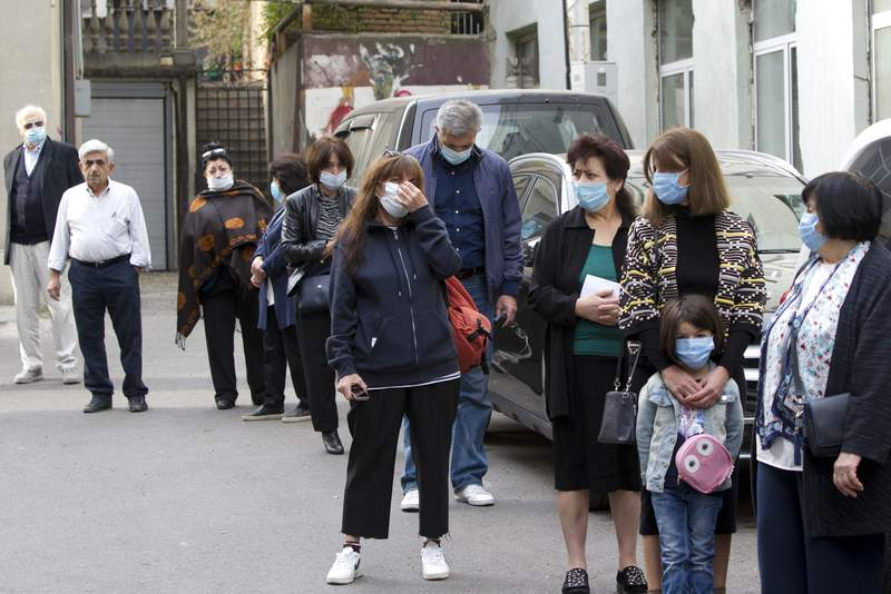 Georgians wearing face masks to help curb the spread of the coronavirus, lineup to vote outside at a polling station during the parliamentary elections in Tbilisi, Georgia on Saturday.