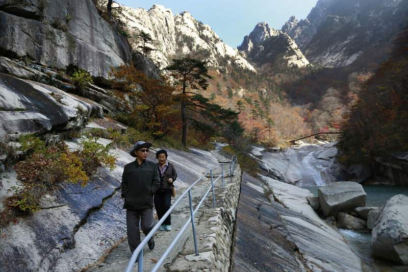 FILE - In this Oct. 23, 2018, file photo, local tourists walk on the trail at Mount Kumgang, known as Diamond Mountain, in North Korea. A top North Korea official has visited the mountain resort that had been jointly run with rival South Korea and discussed efforts to unilaterally rebuild it into a cultural resort envied by the whole world, state media reported Sunday, Dec. 20, 2020. (AP Photo/Dita Alangkara, File)