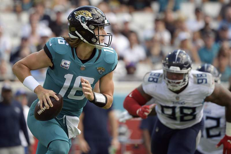 Jacksonville Jaguars quarterback Trevor Lawrence, left, looks for a receiver as Tennessee Titans defensive end Jeffery Simmons (98) rushes during the first half of an NFL football game, Sunday, Oct. 10, 2021, in Jacksonville, Fla. (AP Photo/Phelan M. Ebenhack)