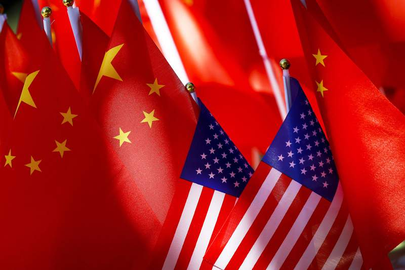 """FILE - In this Sept. 16, 2018, file photo, American flags are displayed together with Chinese flags on top of a trishaw in Beijing. China on Thursday, Dec. 3, 2020 accused critics in the U.S. government of """"an escalation of political suppression"""" against Beijing following a report of new visa restrictions on members of China's ruling Communist Party and their immediate family members. (AP Photo/Andy Wong, File)"""
