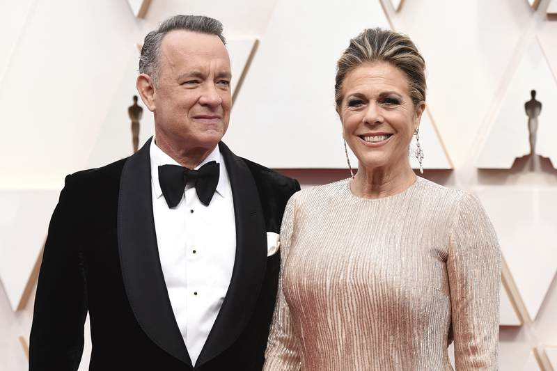 FILE - In this Sunday, Feb. 9, 2020 file photo, Tom Hanks, left, and Rita Wilson arrive at the Oscars at the Dolby Theatre in Los Angeles. On Friday, March 13, 2020, The Associated Press reported on a manipulated image circulating online depicting actor Tom Hanks quarantined at a hospital in Australia with a volleyball that looks like Wilson, his make-believe friend in the movie Cast Away. It first circulated as satire. Hanks is in Australia shooting an Elvis Presley biopic directed by Baz Luhrmann. Hanks shared the news about his positive tests on Twitter Wednesday. (Photo by Jordan Strauss/Invision/AP)