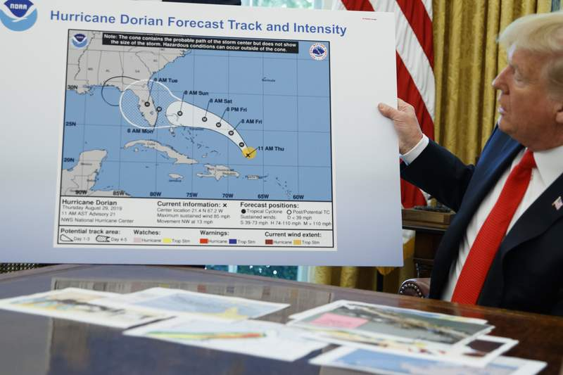 FILE - In this Sept. 4, 2019, file photo, President Donald Trump holds a chart as he talks with reporters after receiving a briefing on Hurricane Dorian in the Oval Office of the White House in Washington. A government watchdog says the Commerce Department is trying to block the findings of an investigation into the agencys role in rebuking forecasters who contradicted President Donald Trumps inaccurate claims about the path of Hurricane Dorian in 2019. (AP Photo/Evan Vucci. File)