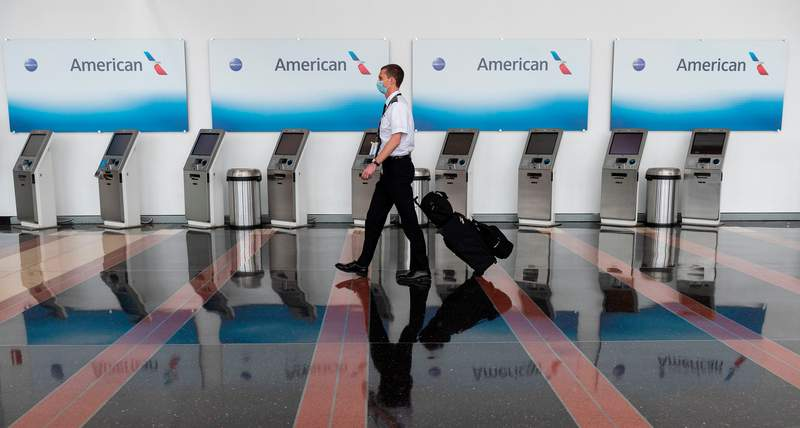 An airline employee walks past empty American Airlines check-in terminals at Ronald Reagan Washington National Airport in Arlington, Virginia.