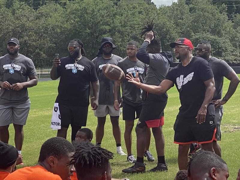Instructors at the Solomon Kindley Football Camp respond to questions from athletes on Saturday morning at Raines High School.