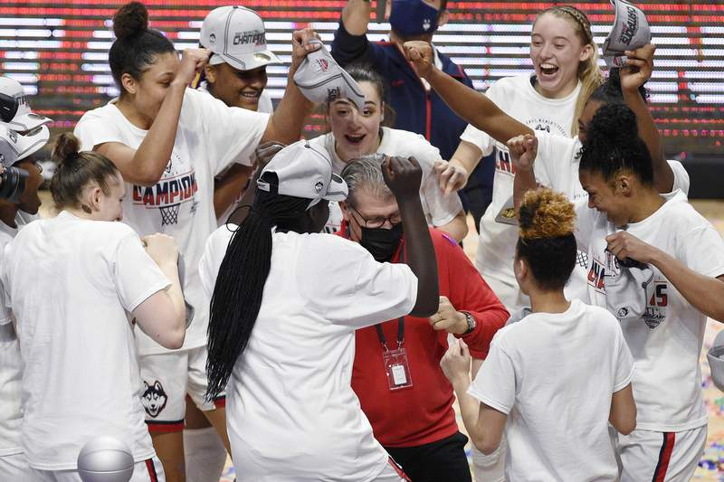 Connecticut head coach Geno Auriemma, center, dances with his team in celebration of their NCAA college basketball game win in the Big East tournament finals against Marquette at Mohegan Sun Arena, Monday, March 8, 2021, in Uncasville, Conn. (AP Photo/Jessica Hill)