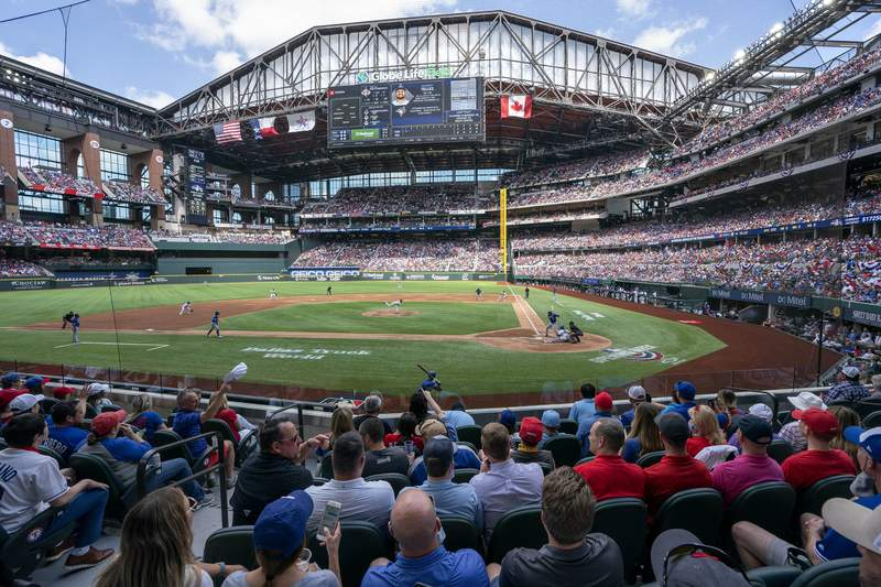 Fans fill the stands at Globe Life Field during the first inning of a baseball game between the Texas Rangers and the Toronto Blue Jays, Monday, April 5, 2021, in Arlington, Texas. The Rangers are set to have the closest thing to a full stadium in pro sports since the coronavirus shutdown more than a year ago. (AP Photo/Jeffrey McWhorter)