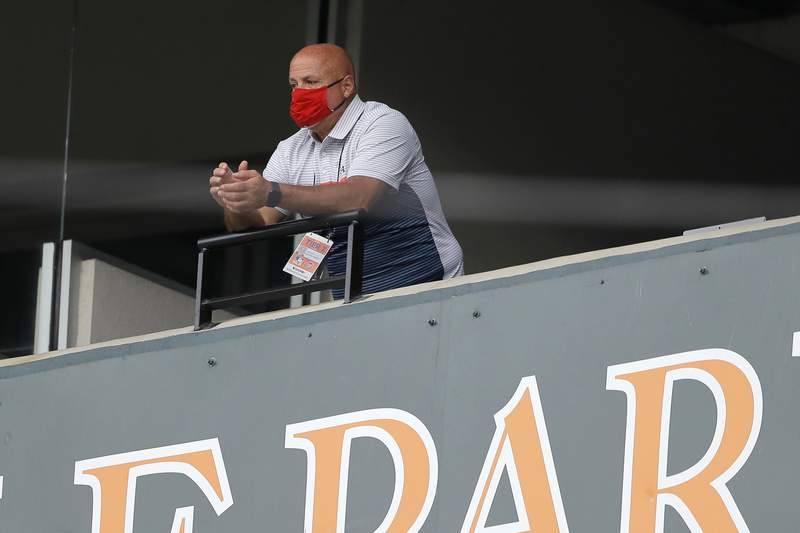 FILE - In this Aug. 14, 2020, file photo, Washington Nationals general manager Mike Rizzo looks on during the seventh inning in the continuation of a suspended baseball game between the Baltimore Orioles and the Nationals in Baltimore. On Wednesday, March 31, 2021, Rizzo said a player for the team has tested positive for COVID-19. Rizzo said that four teammates and a staff member have been quarantined on the eve of the start of the regular season after contact tracing. (AP Photo/Julio Cortez, File)