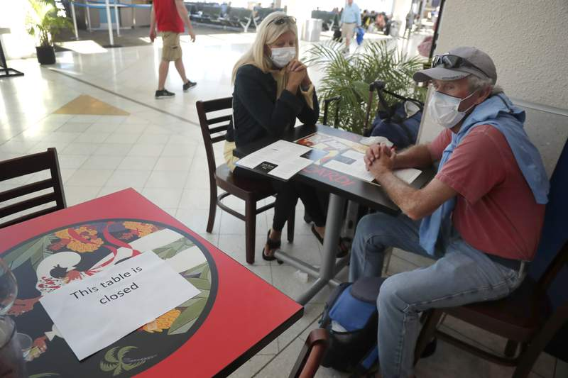 Debra and Barry Fitzpatrick wear masks at an airport pub that is practicing social distancing with widespace table seating due to the coronavirus outbreak. (AP Photo/Elise Amendola)