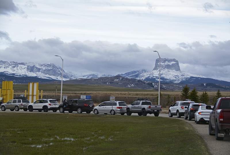 In this Thursday, April 29, 2021, photo, Canadians drive-in at the Piegan-Carway border to receive a COVID-19 from the Blackfeet tribe near Babb, Mont. The Chief Mountain, sacred to the Blackfeet tribe towers, are seen in the background. The Blackfeet tribe gave out surplus vaccines to its First Nations relatives and others from across the border.