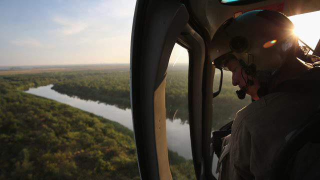 An air interdiction officer with U.S. Customs and Border Protection flies along the Rio Grande at the U.S.-Mexico border near McAllen, Texas. (Photo by John Moore/Getty Images)