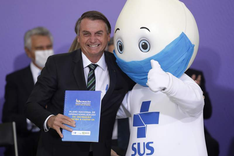 """FILE - In this Dec. 16, 2020 file photo, BrazilIan President Jair Bolsonaro poses for photos with the mascot of the nation's vaccination campaign, named """"Ze Gotinha,"""" or Joseph Droplet, during a ceremony to present Brazil's National Vaccination Plan Against COVID-19, at Planalto presidential palace in Brasilia, Brazil. The Brazilian internet spent the last few days wondering about his apparent disappearance after Brazil's former President Lula joked that he may have been shoved aside due to political motivations. (AP Photo/Eraldo Peres, File)"""