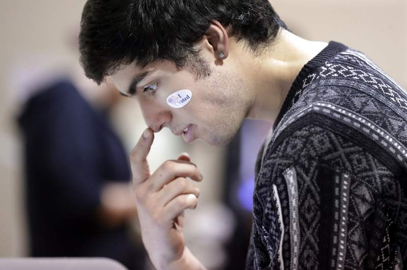 David Flores-Figueroa wears his voting sticker on his face as he reads over the ballot before voting on Super Tuesday at the Cleveland Park Community Center precinct, Tuesday, March 3, 2020, in Nashville, Tenn. Deadly overnight tornadoes delayed the start of the presidential primary voting in Nashville and another Tennessee county, spurring elections officials to redirect voters from some polling places to alternate locations. Voters from six precincts were combined to vote at Cleveland Park, where the wait could take up to an hour or more. (AP Photo/Mark Humphrey)