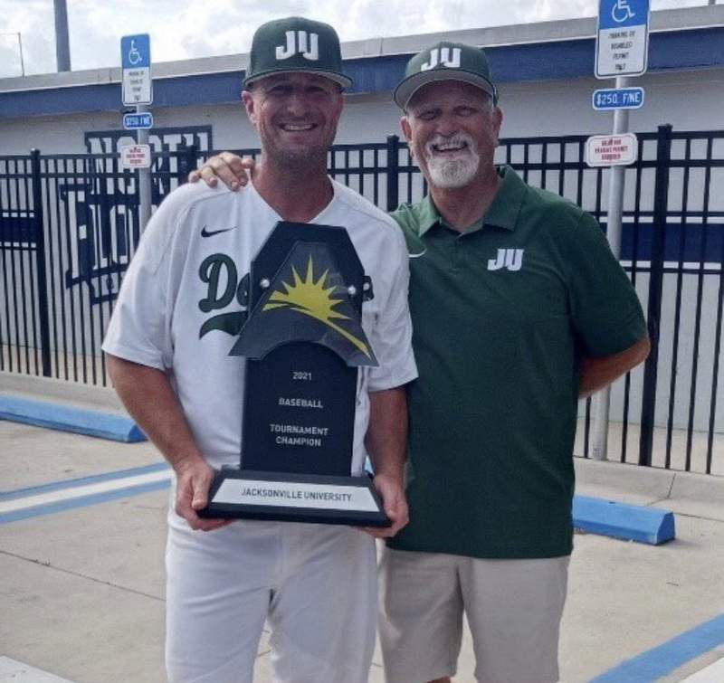 JU baseball coach Chris Hayes (left) poses with the 2021 ASUN tournament championship trophy along with his former coach, Terry Alexander, following the Dolphins win over Liberty Saturday at UNF's Harmon Stadium.