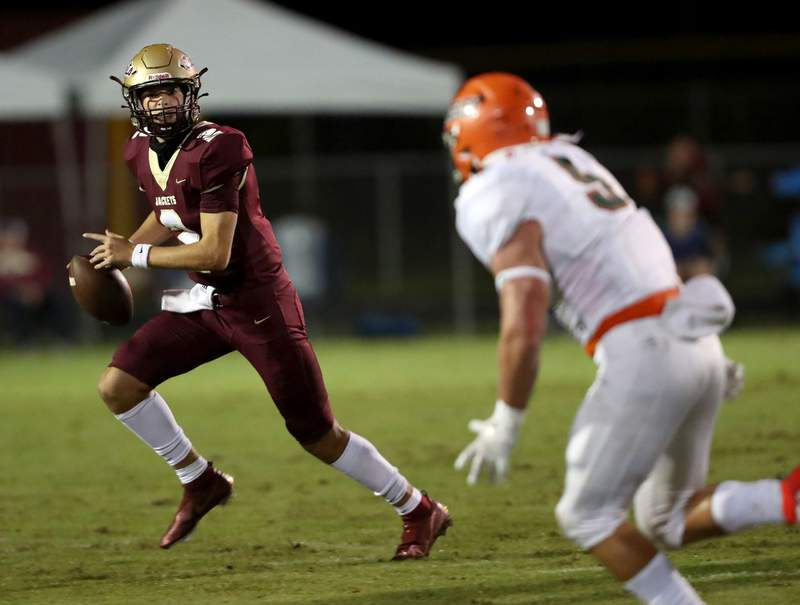 St. Augustine quarterback Sam Edwards rolls out to pass during Friday's 38-24 win over Mosley in the Region 1-6A opener. (Ralph D. Priddy)