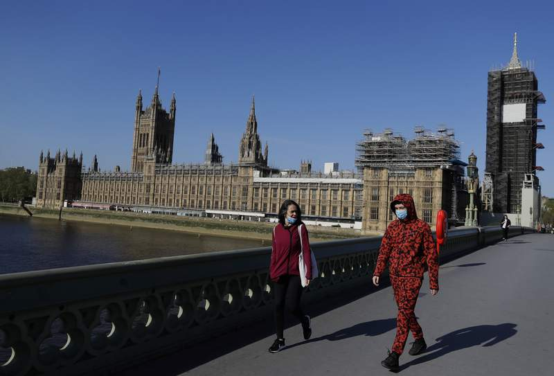 People wear masks as they walk near Britain's Houses of Parliament as the country is in lockdown to help curb the spread of coronavirus, in London, Tuesday, April 21, 2020. Britain's Parliament is going back to work, and the political authorities have a message for lawmakers: Stay away. U.K. legislators and most parliamentary staff were sent home in late March as part of a nationwide lockdown to slow the spread of the new coronavirus. With more than 16,500 people dead and criticism growing of the governments response to the pandemic, legislators are returning Tuesday  at least virtually  to grapple with the crisis.(AP Photo/Kirsty Wigglesworth)