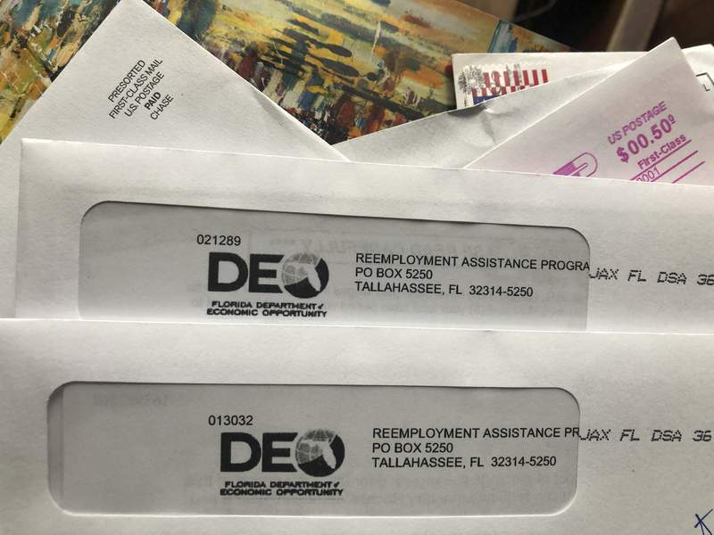 FILE - Envelopes from the Florida Department of Economic Opportunity Reemployment Assistance Program are shown, Thursday, Nov. 5, 2020, in Surfside, Fla. (AP Photo/Wilfredo Lee)