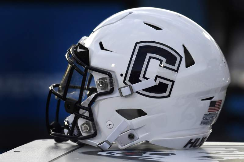 FILE - In this Sept. 7, 2019, file photo, Connecticut football helmet rests on the sideline during an NCAA college football game in East Hartford, Conn. UConn has canceled its 2020-2021 football season, becoming the first FBS program to suspend football because of the coronavirus pandemic.(AP Photo/Jessica Hill, File)