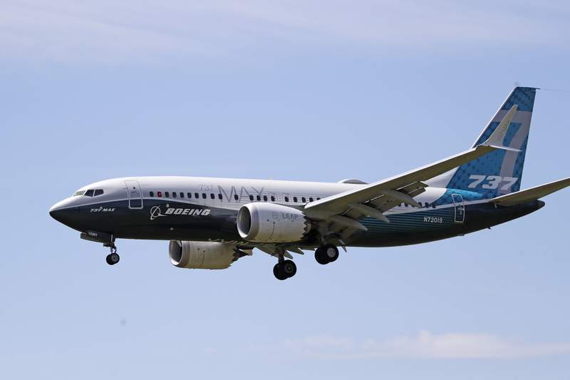 FILE - In this Monday, June 29, 2020, file photo, a Boeing 737 Max jet heads to a landing at Boeing Field following a test flight in Seattle. A U.S. House committee is questioning whether Boeing and the Federal Aviation Administration have recognized problems that caused two deadly 737 Max jet crashes and if either organization will be willing to make significant changes to fix them. (AP Photo/Elaine Thompson, File)