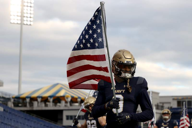 Cameron Kinley of the Navy Midshipmen carries an American flag as the team takes the field against the Tulsa Golden Hurricane at Navy-Marine Corps Memorial Stadium on December 05, 2020 in Annapolis, Maryland. (Photo by Rob Carr/Getty Images)