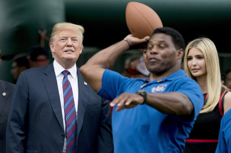 FILE - In this May 29, 2018, file photo, President Donald Trump, left, and his daughter Ivanka Trump, right, watch as former football player Herschel Walker, center, throws a football during White House Sports and Fitness Day on the South Lawn of the White House in Washington. On Tuesday, Aug. 17, 2021, Walker filed paperwork to enter the U.S. Senate race in Georgia after months of speculation, joining other Republicans seeking to unseat Democratic Sen. Raphael Warnock in 2022. (AP Photo/Andrew Harnik, File)
