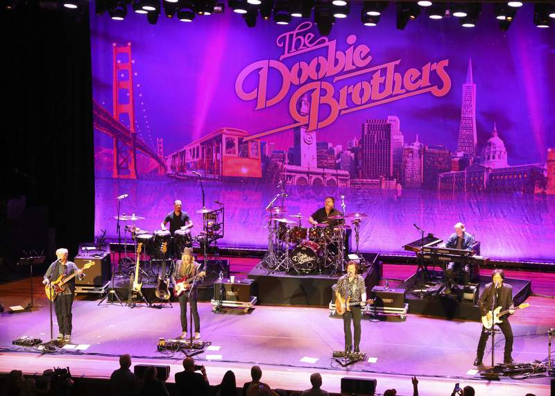 FILE - This Nov. 18, 2019 file photo shows The Doobie Brothers performing at Ryman Auditorium in Nashville, Tenn. The band is rescheduling their 50th anniversary tour because of the coronavirus pandemic. The Rock and Roll Hall of Fame nominees announced Tuesday, May 26, 2020, that the tour, which was to begin in June, will now kick off in July 2021. (Photo by Al Wagner/Invision/AP, File)