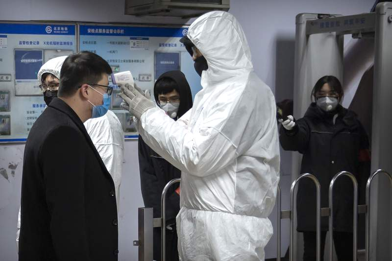 A worker wearing a hazardous materials suit takes the temperature of a passenger at the entrance to a subway station in Beijing, Sunday, Jan. 26, 2020. The new virus accelerated its spread in China, and the U.S. Consulate in the epicenter of the outbreak, the central city of Wuhan, announced Sunday it will evacuate its personnel and some private citizens aboard a charter flight. (AP Photo/Mark Schiefelbein)