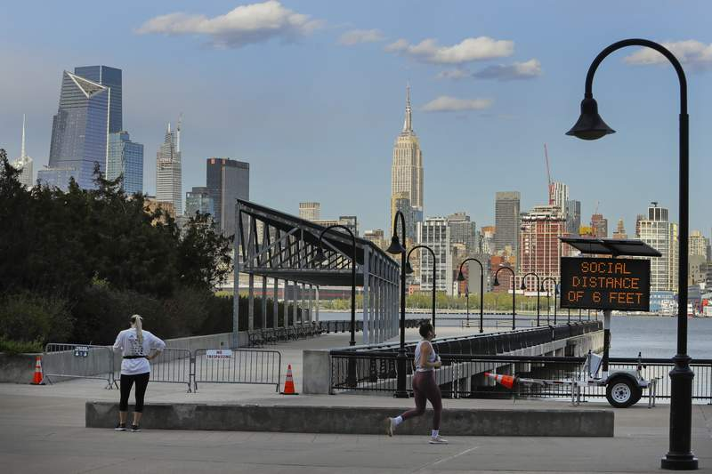 A runner in Maxwell Place Park passes a sign reminding people of social distancing Thursday, May 7, 2020, in Hoboken, N.J., during the coronavirus outbreak. (AP Photo/Frank Franklin II)
