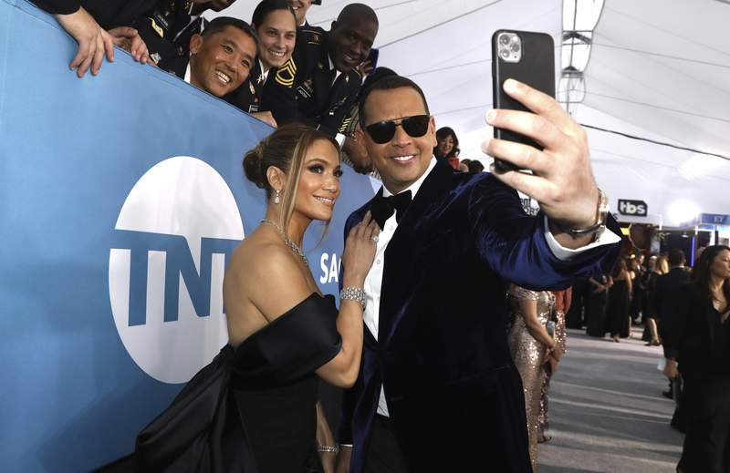 FILE - In this Jan. 19, 2020 file photo, Jennifer Lopez, left, and Alex Rodriguez take a selfie as they arrive at the 26th annual Screen Actors Guild Awards at the Shrine Auditorium & Expo Hall  in Los Angeles.  Lopez and Rodriguez said Saturday, March 13, 2021,  in a statement that reports of their split are inaccurate, and they are working things through. A day earlier, multiple reports based on anonymous sources said the couple had called off their two-year engagement. (Photo by Matt Sayles/Invision/AP, File)