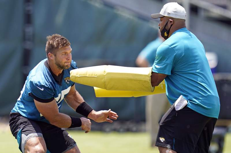 Jacksonville Jaguars tight end Tim Tebow, left, performs a drill during NFL football practice, Thursday, May 27, 2021, in Jacksonville, Fla. (AP Photo/John Raoux)