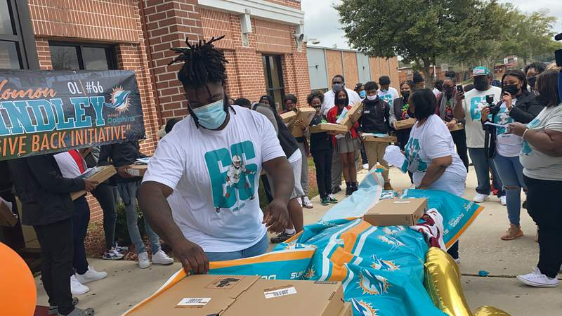 Miami Dolphins rookie offensive lineman Solomon Kindley hands out Lenovo laptop computers to students at Raines on Friday afternoon. Kindley, a 2016 Raines graduate, gave 22 laptops to students there.