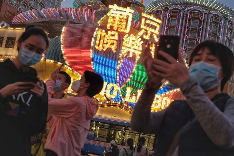 FILE - In this Jan, 23, 2020, file photo released by Initium Media, tourists wearing masks, take photographs outside the Casino Lisboa in Macao, China. The Chinese territory of Macao will allow casinos to reopen Friday, Feb. 21, 2020 after a 15-day closure imposed to help block the spread of China's virus outbreak. (Choi Chi Chio/Initium Media via AP, File)