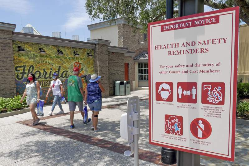 Signs remind patrons to wear masks and other protocols because of the coronavirus pandemic as they stroll through the Disney Springs shopping, dining and entertainment complex Tuesday, June 16, 2020, in Lake Buena Vista, Fla. Walt Disney World Resort theme parks plan to reopen on July 11. (AP Photo/John Raoux)