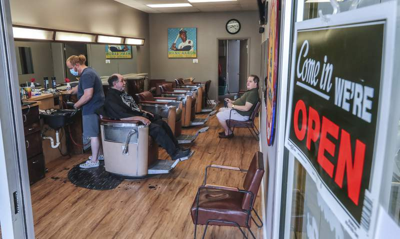 Barber and owner of Chris Edwards, left,  wears a mask and cuts the hair of customer at Peachtree Battle Barber Shop in Atlanta on Friday, April 24, 2020. (John Spink/Atlanta Journal-Constitution via AP)