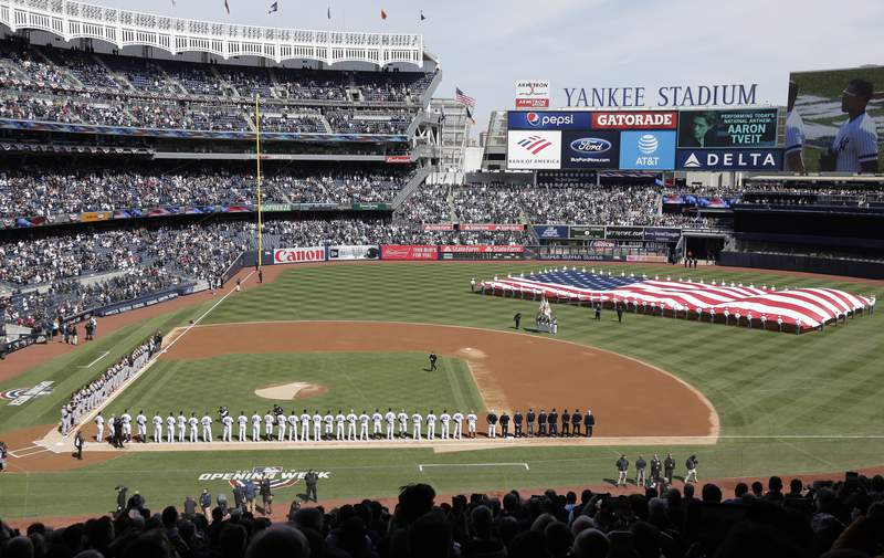 FILE - In this March 28, 2019, file photo, a large flag is unfurled during the national anthem before an opening day baseball game between the New York Yankees and the Baltimore Orioles at Yankee Stadium in New York. Forbes estimates the New York Yankees are baseballs most valuable franchise at $5 billion, up 9% over last year and 47% more than the No. 2 Los Angeles Dodgers at $3.4 billion.(AP Photo/Seth Wenig, File)