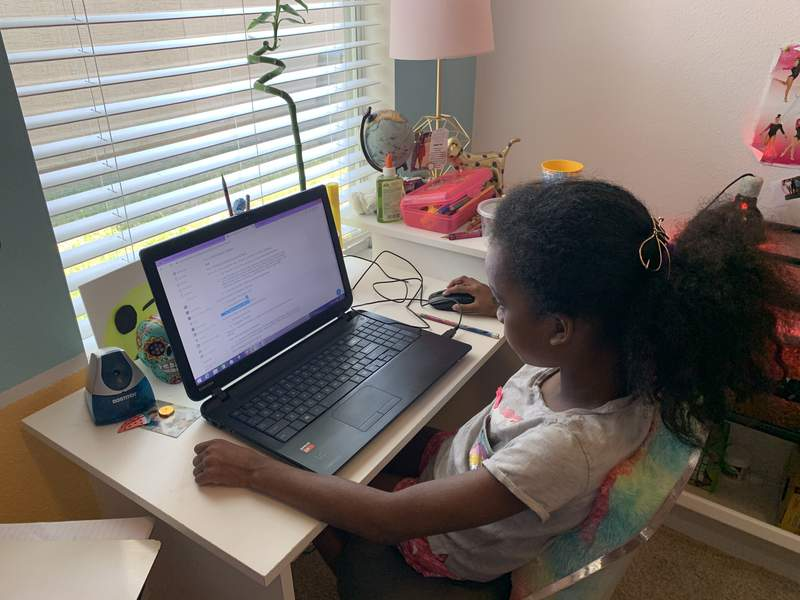 Jiselle Hill, a second-grade student at Timberlin Creek Elementary School in St. Johns County, works on school work in her bedroom.