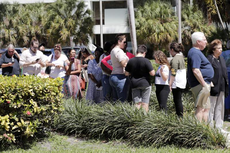 People wait in line to vote in the presidential primary election at the Supervisor of Elections office, Tuesday, March 17, 2020, in Delray Beach, Fla. This polling station was made available after some precincts in Palm Beach County were unable to open after poll workers did not report to work. (AP Photo/Lynne Sladky)
