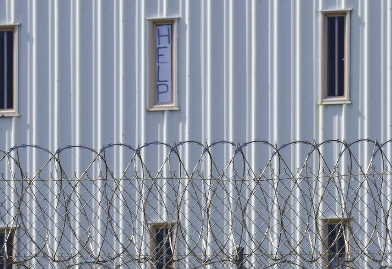 """FILE - In this Oct. 22, 2019, file photo, a sign reads, """"HELP,"""" in the window of an inmate cell seen during a tour by state officials at Holman Correctional Facility in Atmore, Ala. Alabama lawmakers return to Montgomery on Monday, Sept. 27, 2021, to vote on a $1.3 billion prison construction plan proponents say will help address the states longstanding problems in corrections, but critics argue the troubles go much deeper and wont be remedied with brick, mortar and bars. (AP Photo/Kim Chandler, File)"""