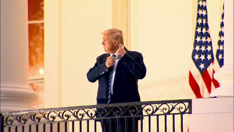 Trump removes his mask upon return to the White House on Monday evening following three days in Walter Reed Military Medical Center.