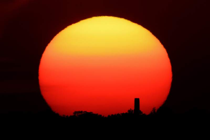 FILE - In this Friday, June 26, 2020 file photo, the sun sets behind a smokestack in the distance in Kansas City, Mo. According to a World Meteorological Organization forecast for the next five years, released on Thursday, May 27, 2021, it'll likely be so hot that there's a 40% chance in the next few years that the globe will push past the temperature limit set by the Paris climate agreement. (AP Photo/Charlie Riedel, File)