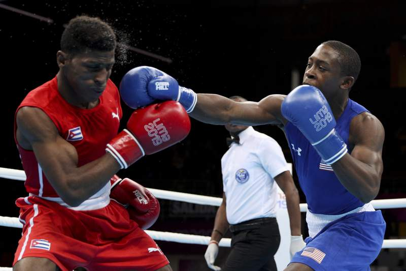 FILE - In this Aug. 2, 2019, file photo, Keyshawn Davis, right, of the United States, hits Andy Cruz, of Cuba, during their men's light welterweight final boxing bout at the Pan American Games in Lima, Peru. When the Tokyo Olympics were postponed, Davis took several weeks to choose his path to boxing stardom. Every member of the U.S. boxing team agrees so far. Even with an extra year to wait, Davis and his 12 teammates are all still focused on Tokyo and the rewards of the Olympic experience. (AP Photo/Martin Mejia, File)