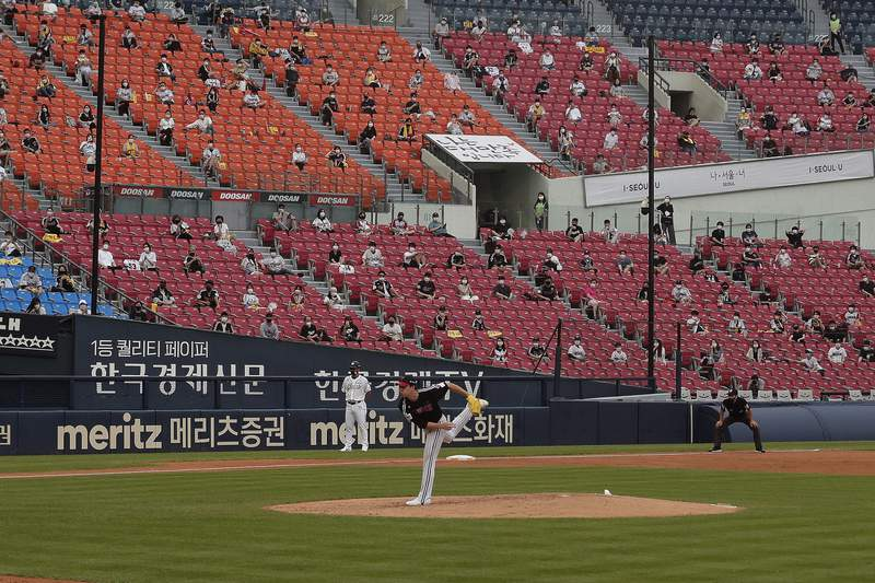Fans wearing face masks to help protect against the spread of the new coronavirus watch the KBO league game between Doosan Bears and LG Twins in Seoul, South Korea, Sunday, July 27, 2020. Masked fans hopped, sang and shouted cheering slogans in baseball stadiums in South Korea on Sunday as authorities began bringing back spectators in professional sports games amid the coronavirus pandemic. (AP Photo/Ahn Young-joon)