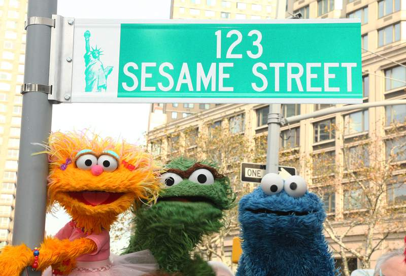 """Sesame Street characters pose under a """"123 Sesame Street"""" sign."""