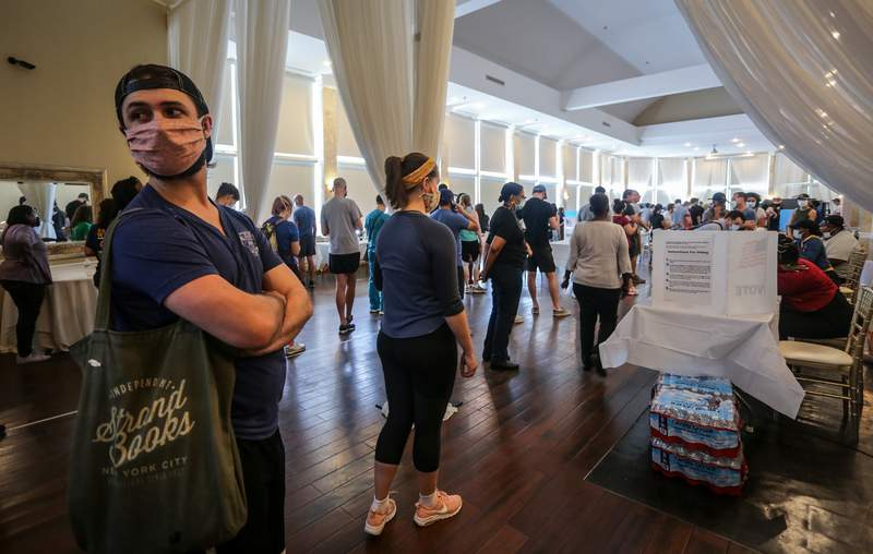Voters wait in line to cast their ballots in the state's primary election at a polling place in Atlanta, where some voting machines went dark and voters were left standing in long lines in humid weather.