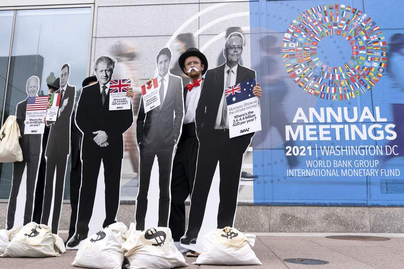 Activists holding a cardboard cutouts of President Joe Biden, Canadian Prime Minister Justin Trudeau, Australian Prime Minister Scott Morrison, Britain's Prime Minister Boris Johnson and Italian Prime Minister Mario Draghi protest outside of the International Monetary Fund headquarters during the World Bank/IMF Annual Meetings in Washington, Wednesday, Oct. 13, 2021. (AP Photo/Jose Luis Magana)