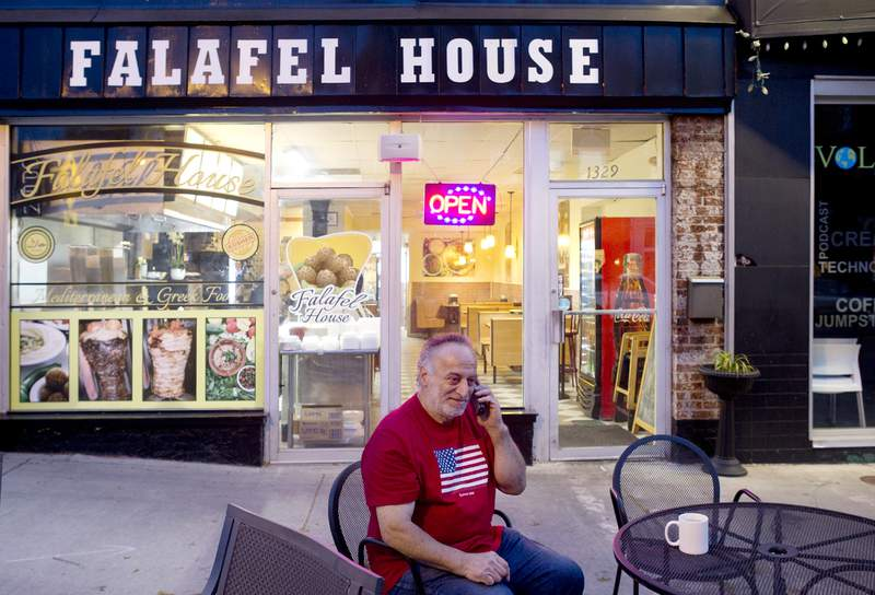 Clade Karim takes a take out order over the phone for Falafel House in downtown Grandin on Monday night, March 30, 2020. Karim is friends with the owner and is a self proclaimed volunteer helper for the restaurant. (Heather Rousseau/The Roanoke Times via AP)