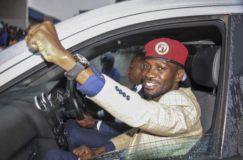 FILEIn this file photo of Thursday Jan.9, 2020, Ugandan presidential hopeful and political activist Bobi Wine, whose real name is Kyagulanyi Ssentamu, raises his fist in the air to gathered supporters as he leaves after meeting with the Electoral Commission, in Kampala, Uganda.  A bodyguard for Ugandan opposition leader Bobi Wine was killed and two journalists injured on Sunday, Dec. 27,  amid violent confrontations between security forces and followers of the singer and lawmaker who is challenging the country's long-time leader. A tearful Wine, whose real name is Kyagulanyi Ssentamu, said his bodyguard had died of his injuries after allegedly being run over by a truck belonging to the military police.  (AP Photo/Ronald Kabuubi-File)
