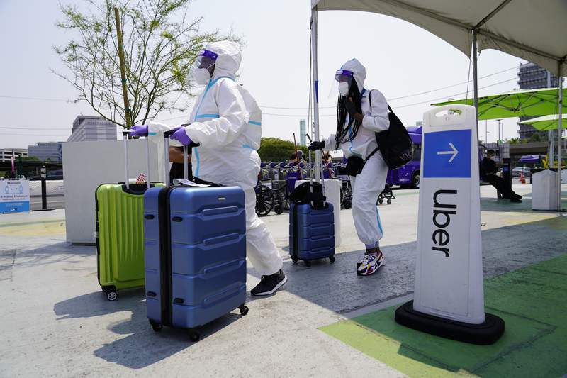 FILE - Travelers, Kerri Ann Salomon, left, and a friend arriving from New York City, look for an Uber ride at Los Angeles InternationalAirport, in this Thursday, Aug. 20, 2020, file photo. Uber is trying to lure drivers with sign-up bonuses and other incentives as it faces record demand for rides and meal delivery. The San Francisco-based ride-hailing company said Monday, April 12, 2021, that its bookings reached an all-time monthly high in March. (AP Photo/Damian Dovarganes, File)
