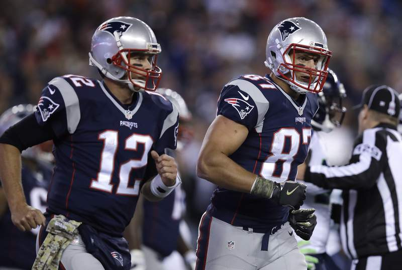 FILE - In this Nov. 13, 2016, file photo, New England Patriots quarterback Tom Brady (12) and tight end Rob Gronkowski head to the sideline during the team's NFL football game against the Seattle Seahawks in Foxborough, Mass. Gronkowski has agreed to a reunion with Brady. The agent for the retired New England star confirmed Tuesday, April 21, 2020, that pending completion of a physical, Gronkowski has agreed to play for the Tampa Bay Buccaneers, who are acquiring his rights from the Patriots. (AP Photo/Charles Krupa, File)