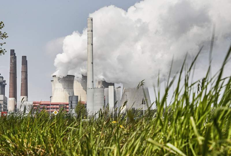 FILE - In this Thursday, April 29, 2021 file photo, a coal-fired RWE power plant steams on a sunny day in Neurath, Germany. The International Energy Agency is urging governments to make stronger commitments to cut greenhouse gas emissions at an upcoming U.N. climate summit. The 30-country organization said Wednesday, Oct. 13 in its annual world energy outlook that the economic rebound from the COVID-19 pandemic also has seen an increase in the use of coal and oil as well as a leap in emissions. (AP Photo/Martin Meissner, file)